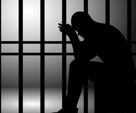 A man waiting on a bail bondsman to get them out of jail.